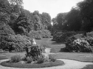 View of the gardens c.1930 showing the Deepdene Coade stone lion. © Surrey History Centre