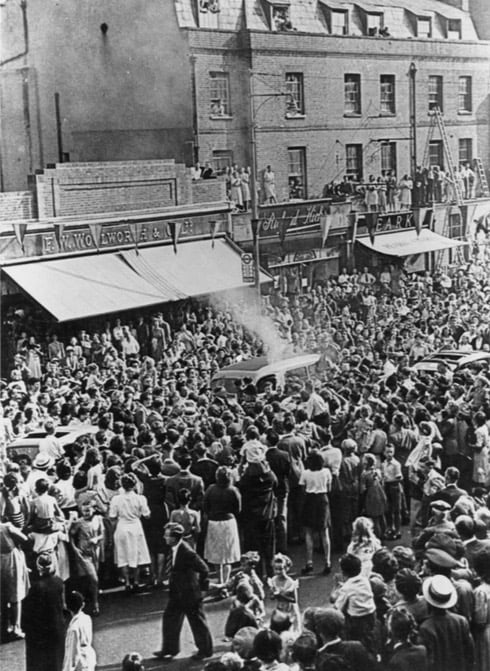 Every vantage point in the High Street is taken as the torch runners are engulfed by the crowd during the transfer of the flame. © Dorking Museum